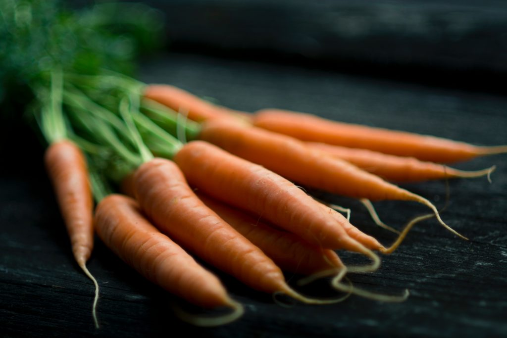 bunch of carrots together on a dark table