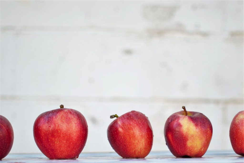 five apples on a white table