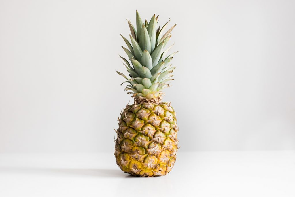 fresh pineapple sitting on a white table and white background