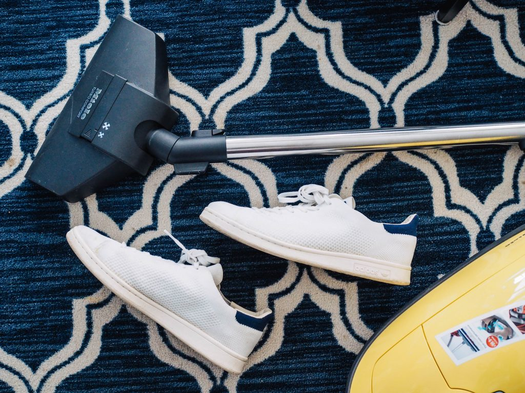 vacuum cleaner lying on blue rug next to white shoes