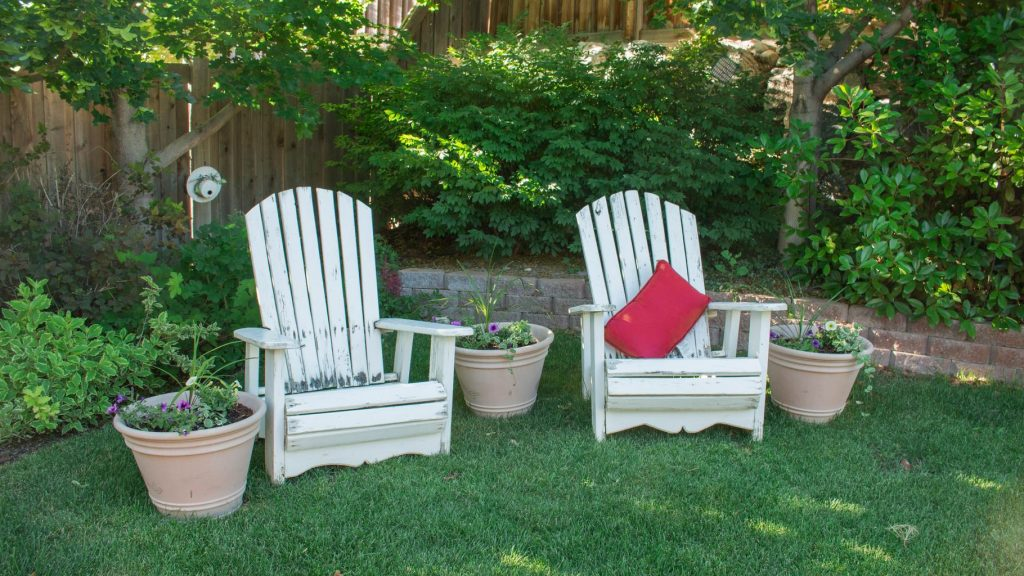 white wooden chairs sitting on green grass in a garden