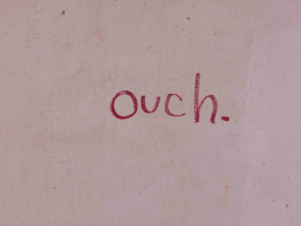 the word ouch written in red on a white wall background